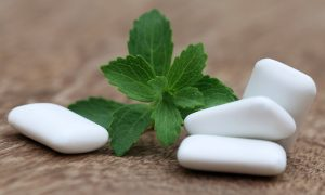Pieces of chewing gum next to mint leaves