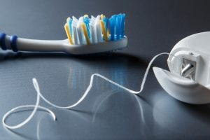 Toothbrush and dental floss on dark background