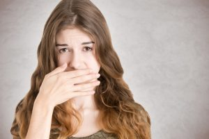 A woman covering her mouth.